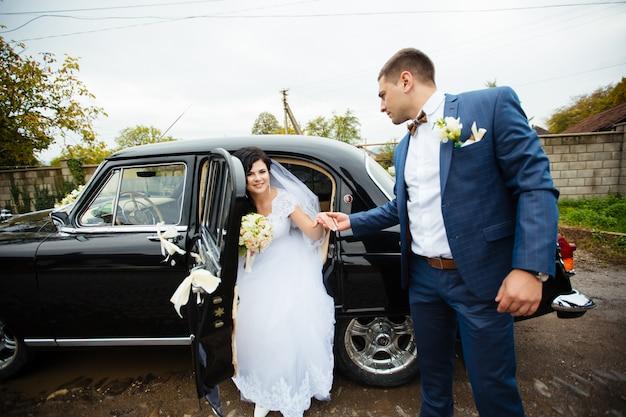 Jeunes mariés près de la voiture classique. ils sont heureux