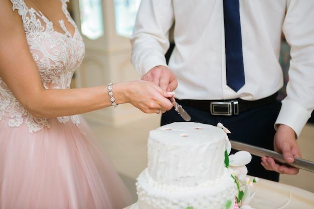 Jeunes mariés à la réception de mariage couper le gâteau de mariage blanc