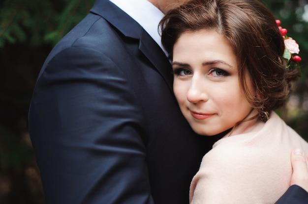 Jeunes mariés s'embrassant dans une forêt dans la forêt d'automne