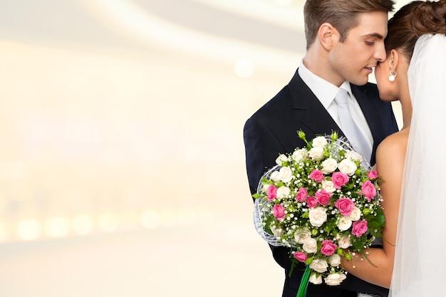 Jeunes mariés s'embrassant sur fond clair