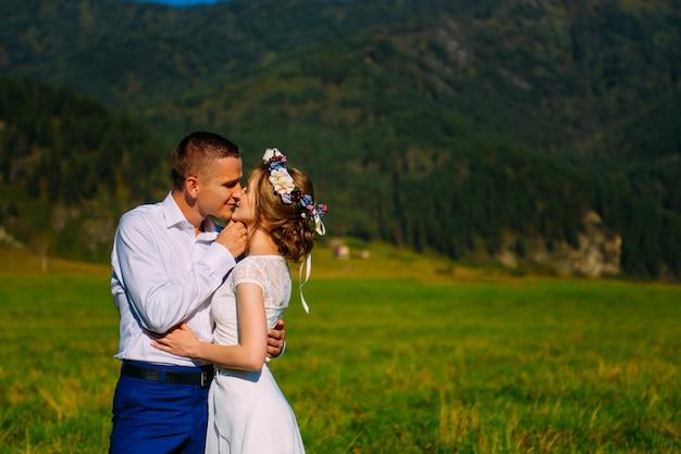 Jeunes mariés s'embrassant sur le pré à l'arrière-plan des montagnes