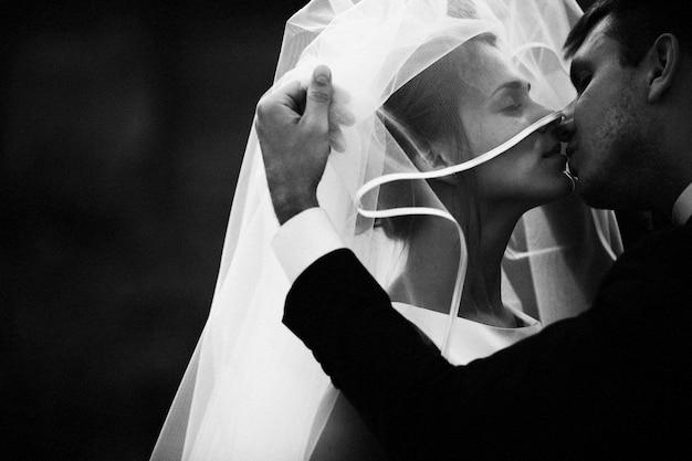 Jeunes mariés s'embrassant sous le voile
