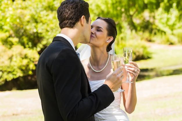 Jeunes mariés s'embrassant tout en grillant des flûtes à champagne