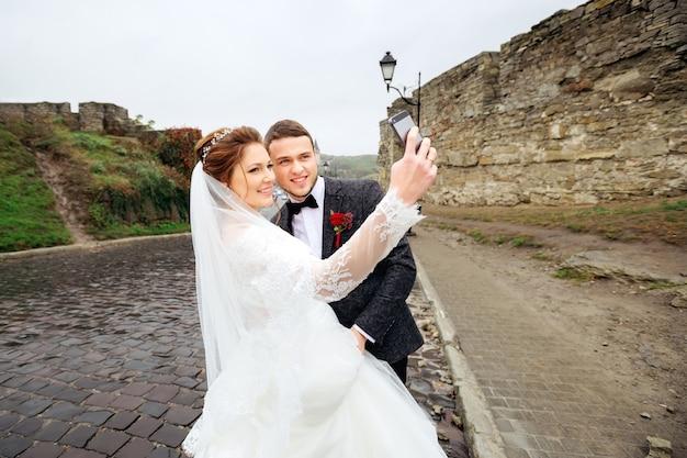 Les jeunes mariés se photographient sur le fond d'un mur de pierre