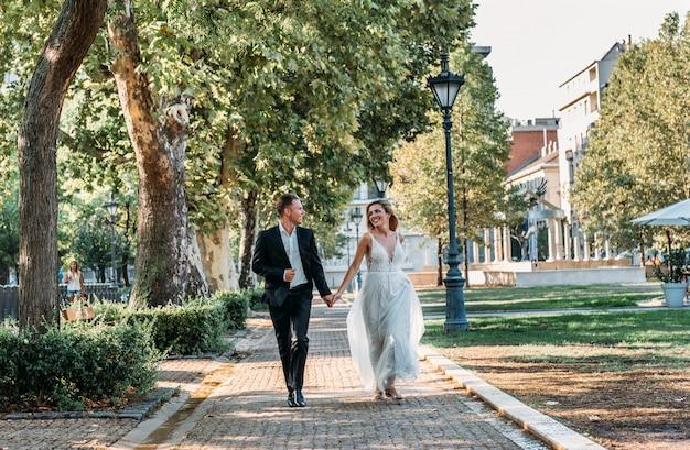 Jeunes mariés se serrant dans la rue de la vieille ville. couple de mariage amoureux. robe de luxe en strass. jours d'été chauds.