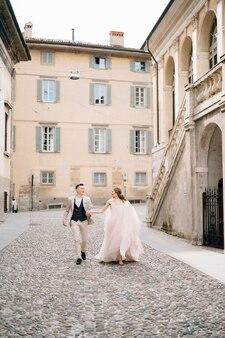 Les jeunes mariés se tenant la main en marchant sur les pavés près de l'ancien bâtiment à bergame italie