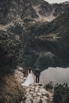 Les jeunes mariés se tiennent au milieu d'une forêt dense et sombre