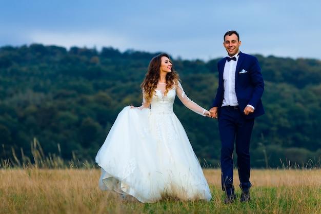 Les jeunes mariés se tiennent la main et marchent sur la pelouse