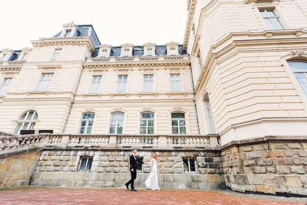 Les jeunes mariés se tiennent la main et marchent près du magnifique palais. ancien palais avec une belle architecture et de nombreuses fenêtres.