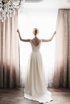 Jeunes mariés sont debout contre la fenêtre donnant sur l'extérieur