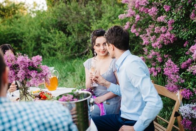 Jeunes mariés à une table de mariage avec des amis dans un jardin printanier