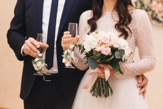 Jeunes mariés tenant des lunettes de mariage joliment décorées avec champagne