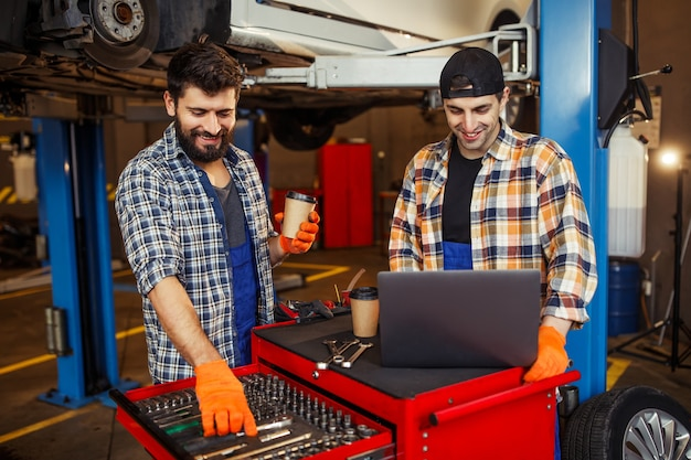 Jeunes mécaniciens travaillant dans le centre de service automobile en buvant du café