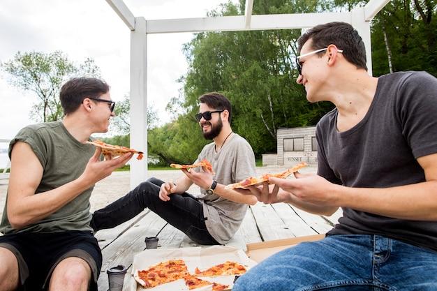 Jeunes mecs avec des morceaux de pizza converser sur la plage