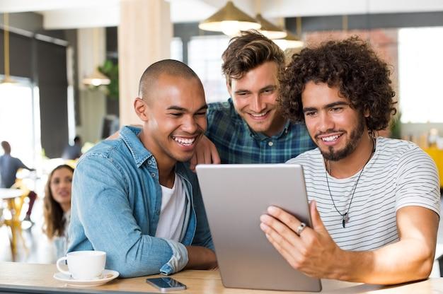 Jeunes mecs en vêtements décontractés souriant et discutant des idées à l'aide de la tablette au café