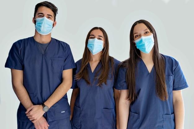 Jeunes médecins dentistes avec des masques en uniforme bleu foncé debout dans le couloir