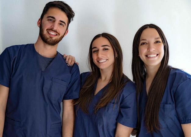 Jeunes médecins dentistes souriants en uniforme bleu foncé debout dans le couloir