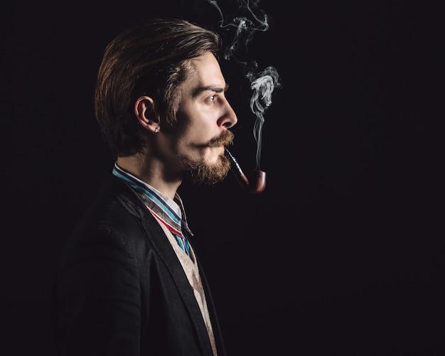 Jeunes messieurs fume une pipe