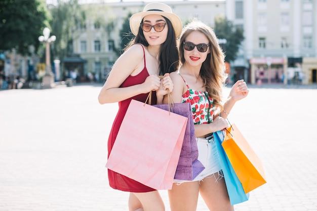 Jeunes modèles confiants avec des sacs en papier brillant