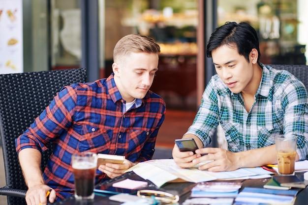 Jeunes multiethniques en chemises à carreaux se réunissant à table de café et discutant de la nouvelle application de voyage sur smartphone