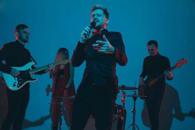 Jeunes musiciens caucasiens, groupe jouant au néon sur fond bleu studio