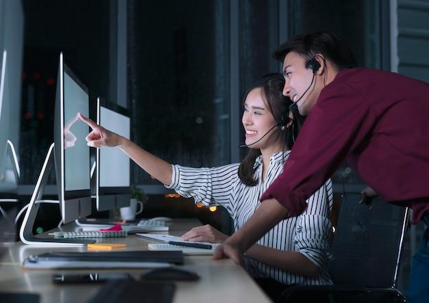 Les jeunes opérateurs de services à la clientèle asiatique thaïlandaise travaillant de nuit dans un centre d'appels pour aider le client d'assistance sur le lieu de travail pendant la nuit