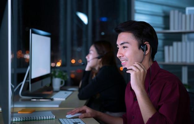 Les jeunes opérateurs de services à la clientèle asiatiques thaïlandais travaillant de nuit dans un centre d'appels