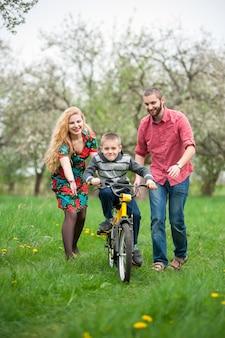 Jeunes parents apprennent à leur fils à faire du vélo