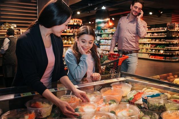 Jeunes parents et fille en épicerie choisissant une salade