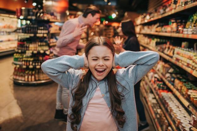 Jeunes parents et fille en épicerie. fille hurlant et pleurant. elle garde les oreilles fermées. ses parents se disputent et se querellent derrière.