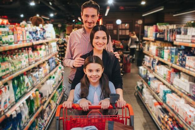 Jeunes parents et fille en épicerie poussant un graphique