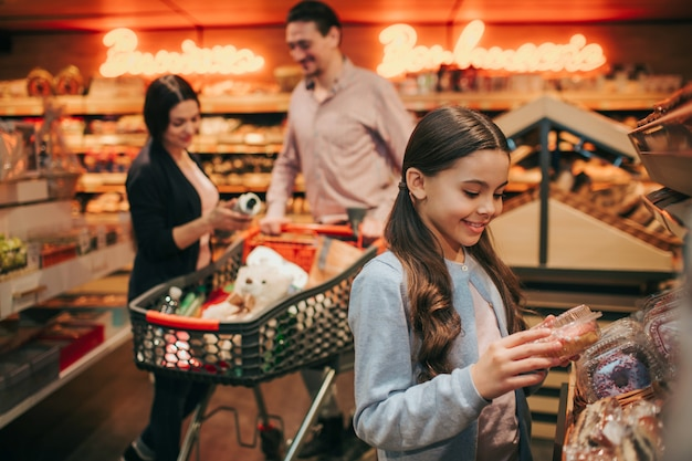 Jeunes parents et fille en épicerie