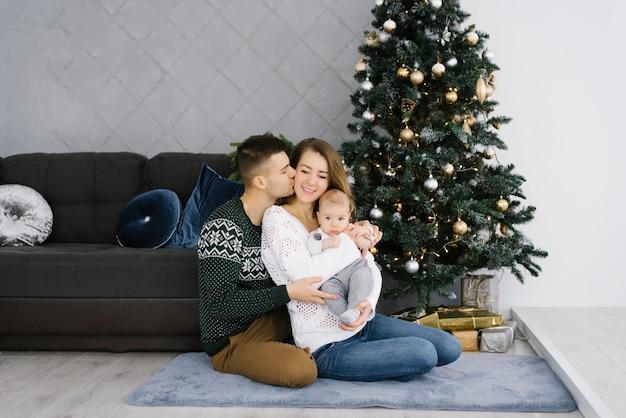 Jeunes parents heureux avec un jeune fils dans ses bras assis à l'arbre de noël. mari embrasse sa femme sur la joue