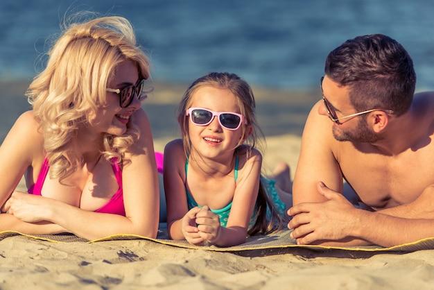 Jeunes parents et leur fille sur la plage.
