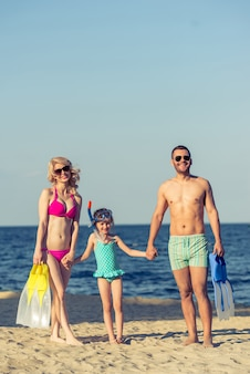 Jeunes parents et leur petite fille à lunettes de soleil.