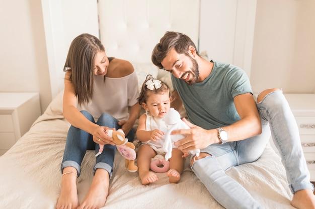 Jeunes parents montrant des jouets à leur fille