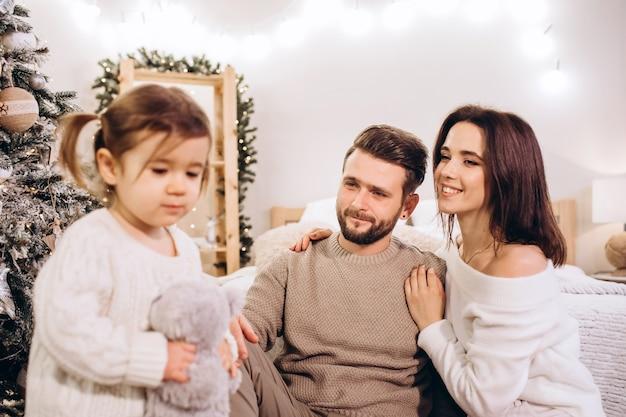 Jeunes parents avec une petite fille près de l'arbre de noël