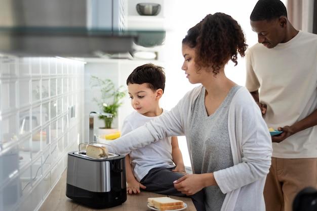 Jeunes parents préparant des toasts avec son fils