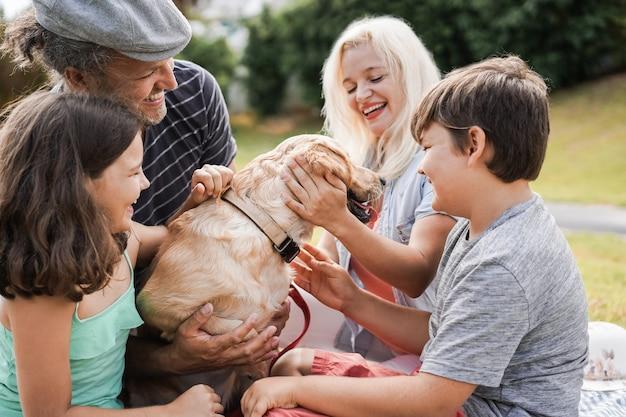 Jeunes parents s'amusant avec les enfants et leur animal de compagnie en plein air au parc en été