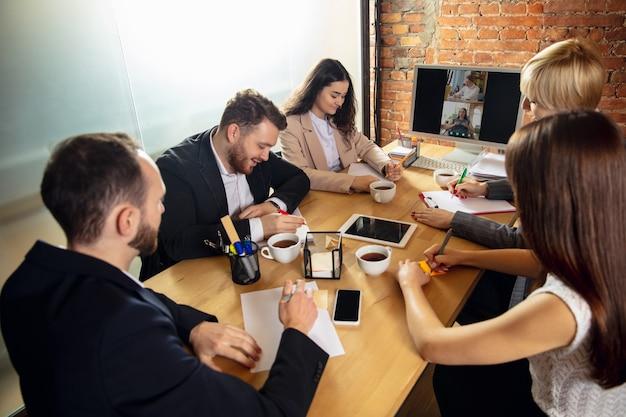 Jeunes parlant en travaillant lors d'une vidéoconférence avec des collègues au bureau ou dans le salon