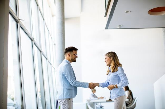 Jeunes partenaires commerciaux faisant la poignée de main dans un bureau pendant que leur équipe travaille en arrière-plan