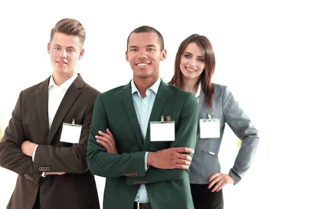Les jeunes participants de la conférence avec des badges vierges, debout au bureau