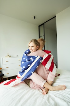 Jeunes patriotes assis sur le lit dans une étreinte enveloppée dans le drapeau américain