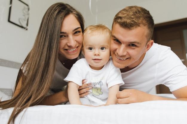 Les jeunes père et mère sont heureux dans les bras de leur enfant