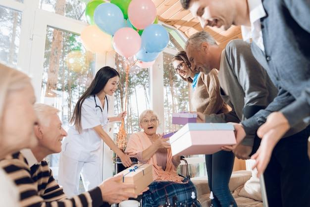 Les jeunes et les personnes âgées sont féliciter une femme âgée.