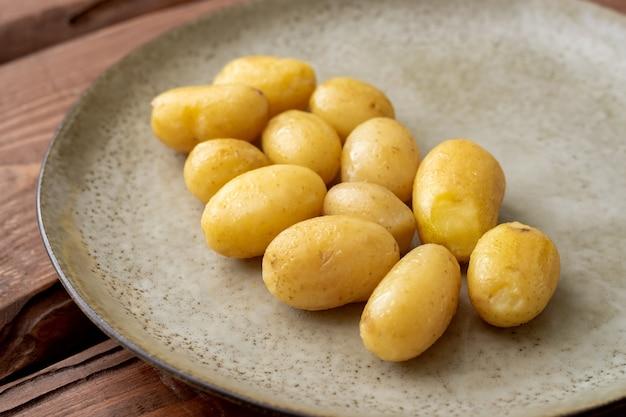 Jeunes petites pommes de terre bouillies sur une assiette sur un fond en bois.