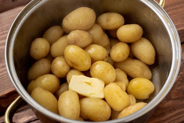 Jeunes petites pommes de terre fraîchement cuites dans une casserole avec du beurre sur un fond en bois.