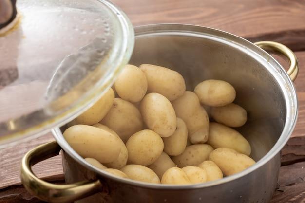 Jeunes petites pommes de terre fraîchement cuites dans une casserole avec de la vapeur sur un fond en bois.