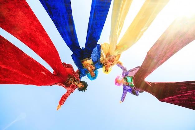 Jeunes sur pilotis posant contre le ciel bleu.