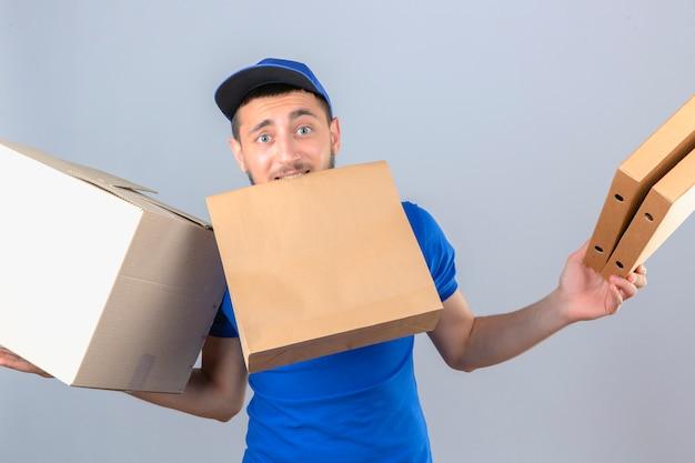 Les jeunes plus tendu livreur portant un polo bleu et une casquette debout avec des paquets confus sur fond blanc isolé